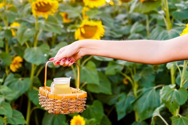 Weibliche hand, die einen weidenkorb mit einem krug sonnenblumenöl auf dem hintergrund des feldes hält. ernte-konzept