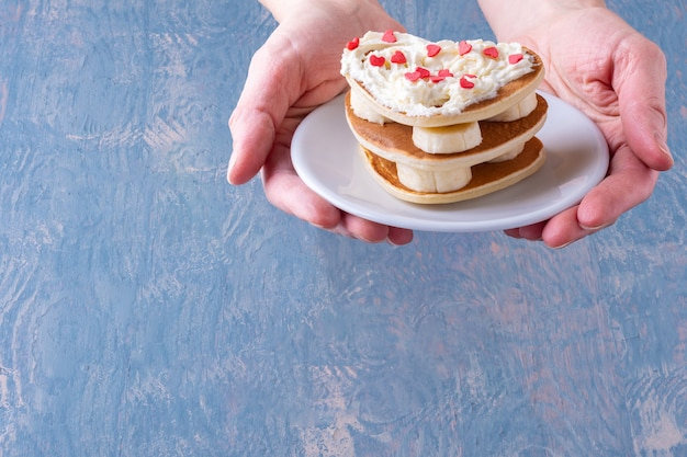 Weibliche hand, die einen weißen teller mit einem stapel hausgemachter herzförmiger pfannkuchen hält, verziert mit weißer creme mit roten herzen und bananenfüllung auf einem blauen hölzernen hintergrund
