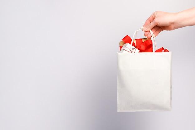 Weibliche hand, die einkaufstasche mit geschenkboxen auf grauem hintergrund hält