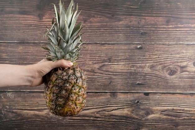 Weibliche hand, die einzelne frische ananas auf hölzernem hintergrund hält