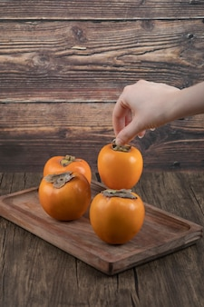 Weibliche hand, die einzelne kakifrucht auf holzoberfläche nimmt