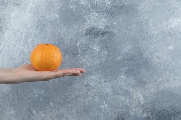 Weibliche hand, die einzelne orange auf marmortisch hält.