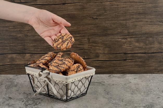 Weibliche hand, die frisch gebackene kekse vom korb auf marmoroberfläche nimmt.