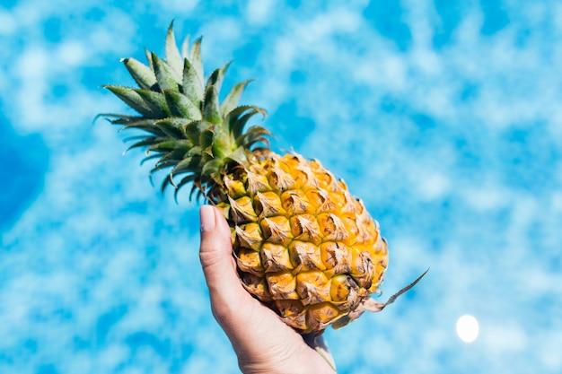 Weibliche hand, die frische ananas im swimmingpool im hotel hält.
