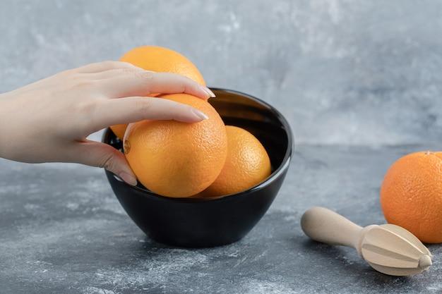 Weibliche hand, die frische orange aus schwarzer schüssel nimmt.
