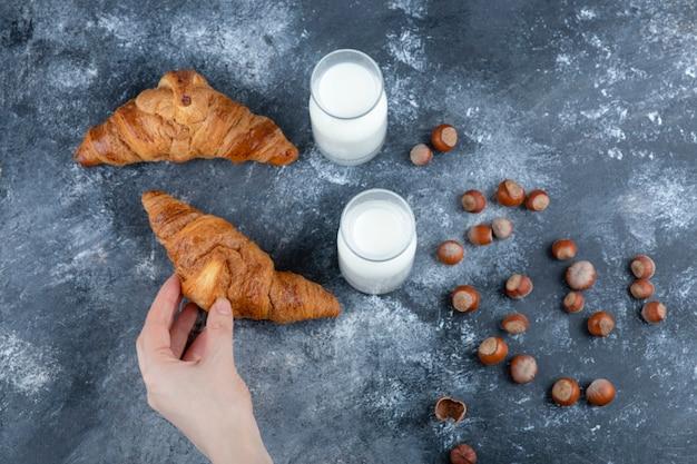 Weibliche hand, die frisches aromatisches croissant auf marmortisch hält.