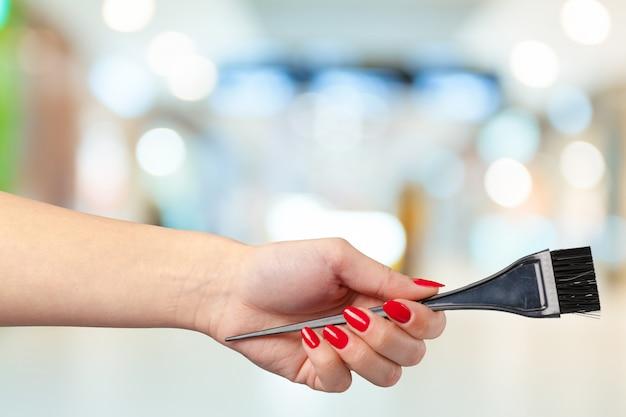 Weibliche hand, die friseurkamm im kosmetischen speicher hält