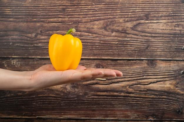 Weibliche hand, die gelben paprika auf hölzerner oberfläche hält