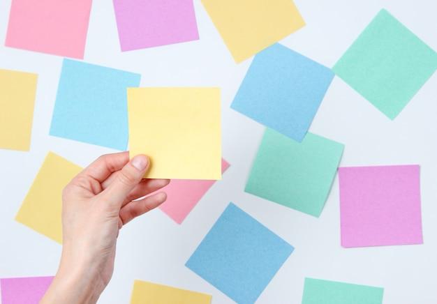 Weibliche hand, die gelbes notizblatt des papiers auf einem weiß unter vielen farbigen blättern des papiers hält