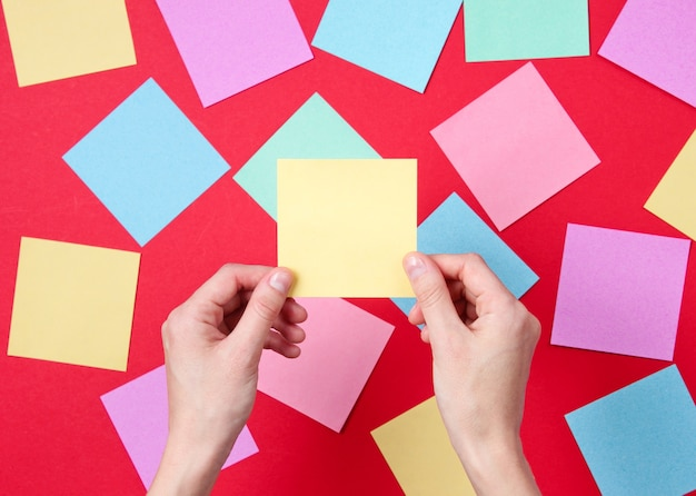 Weibliche hand, die gelbes notizblatt des papiers auf rot unter vielen farbigen blättern des papiers hält