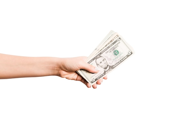 Weibliche hand, die geld auf weißem lokalisiertem hintergrund gibt. draufsicht auf dollar-banknoten. bestechungskonzept. schulden- und darlehenskonzept.