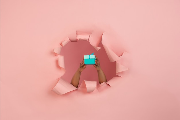 Weibliche hand, die geschenk in zerrissenem korallenrotem rosa papierloch gibt giving