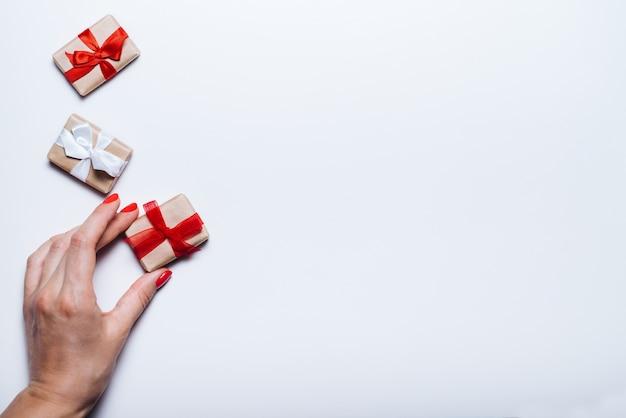 Weibliche hand, die geschenkbox mit rotem band auf leerem weißem hintergrund hält