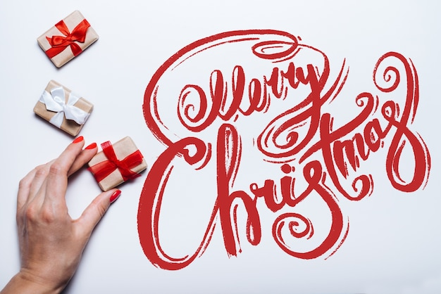 Weibliche hand, die geschenkboxen und frohe weihnachtswünsche hält, die mit kalligraphischer schrift geschrieben werden. draufsicht, flach liegen.
