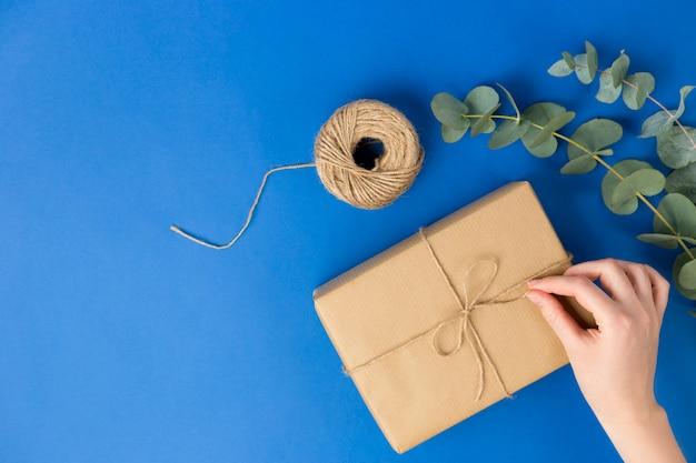 Weibliche hand, die geschenkboxpaket und eukalyptusblätter vorbereitet