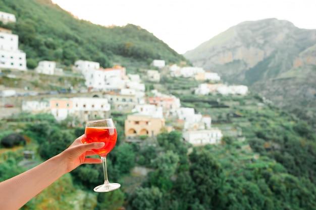 Weibliche hand, die glas mit spritz aperol-alkoholgetränk auf schönem altem italienischem dorf auf amalfi-küste hält