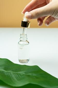 Weibliche hand, die glasflasche ohne marke mit serum für haut hält. kosmetologie- und schönheitskonzept.