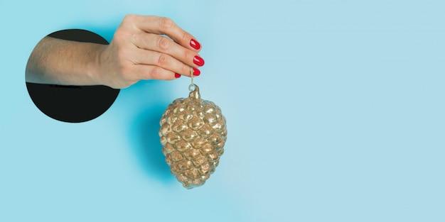 Weibliche hand, die goldenen dekorativen kegel durch rundes loch im blau hält. einladung zur weihnachtsfeiertagsfeier.