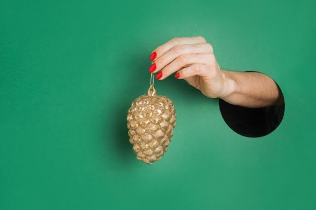 Weibliche hand, die goldenen dekorativen kegel durch rundes loch im grünbuch hält. einladung zur weihnachtsfeiertagsfeier.