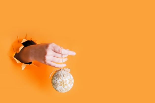Weibliche hand, die goldweihnachtsdekorations-baumflitter durch ein loch auf safran hält. neujahr feierlichkeiten