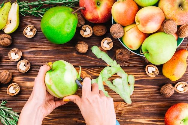 Weibliche hand, die grünen apfel mit schäler abzieht