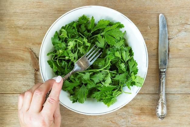 Weibliche hand, die grünen kräutersalat vom alten holztisch des plateons isst