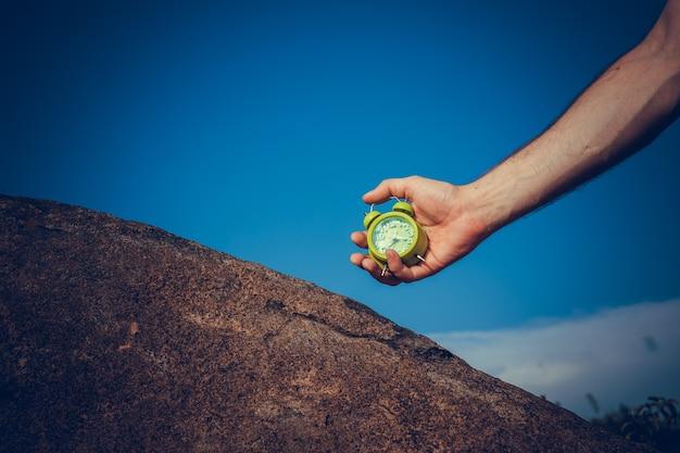 Weibliche hand, die grünen wecker auf blauem hintergrund hält, nahaufnahme.