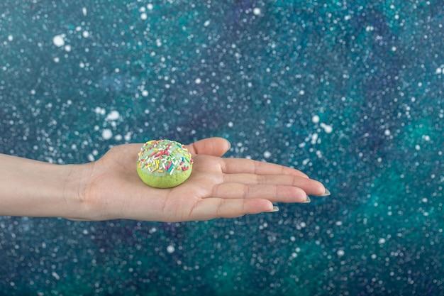 Weibliche hand, die grünes plätzchen mit streuseln hält.