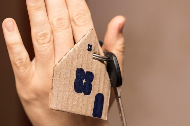 Weibliche hand, die hausschlüssel, immobilienmakler hält.