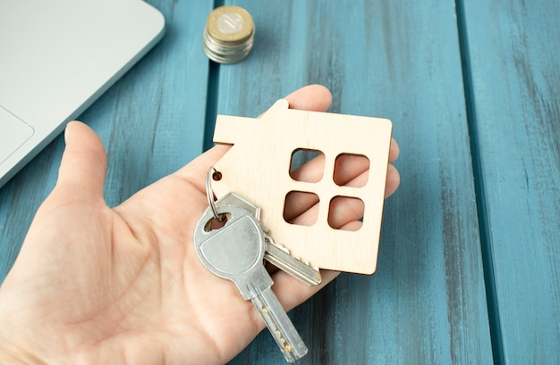 Weibliche hand, die hausschlüssel, immobilienmakler hält