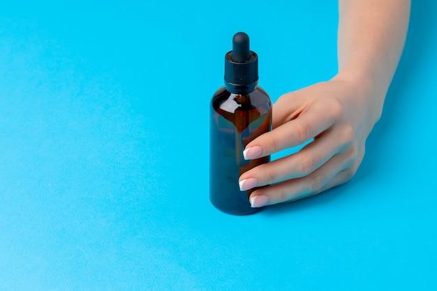 Weibliche hand, die hautpflegeproduktflasche auf blau hält