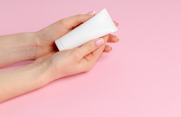 Weibliche hand, die hautpflegeproduktflasche auf rosa hält