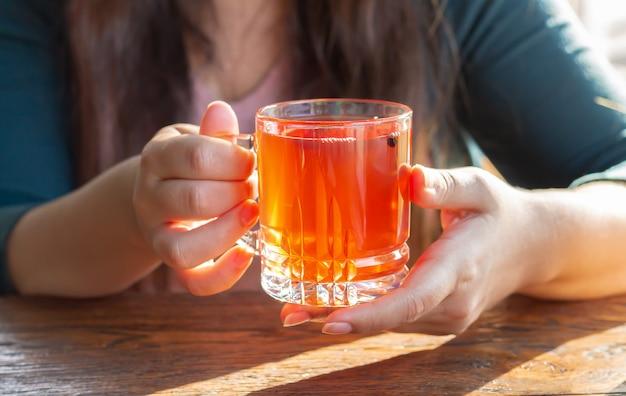 Weibliche hand, die heiße tasse fruchttee am sonnigen morgen hält