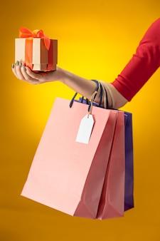 Weibliche hand, die helle einkaufstaschen auf gelb hält