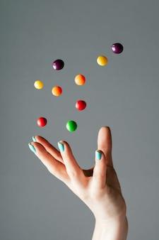 Weibliche hand, die helle, mehrfarbige runde bonbons in die luft wirft, die den süßigkeitenkopierraum vertikal schweben lässt