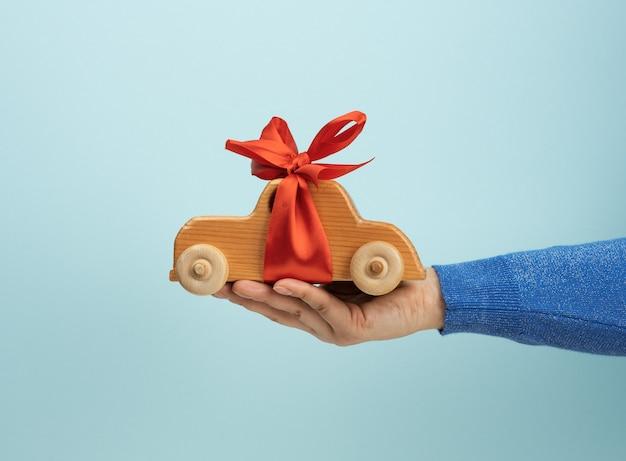 Weibliche hand, die hölzernes spielzeugauto mit rotem band, autoversicherungskonzept, darlehen hält