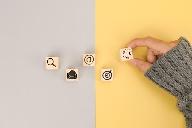Weibliche hand, die holzblock mit ikonengeschäftsidee anordnet