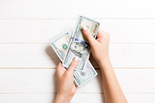 Weibliche hand, die hundert dollarbanknoten auf hölzernem hintergrund gibt. draufsicht des reichtumskonzeptes