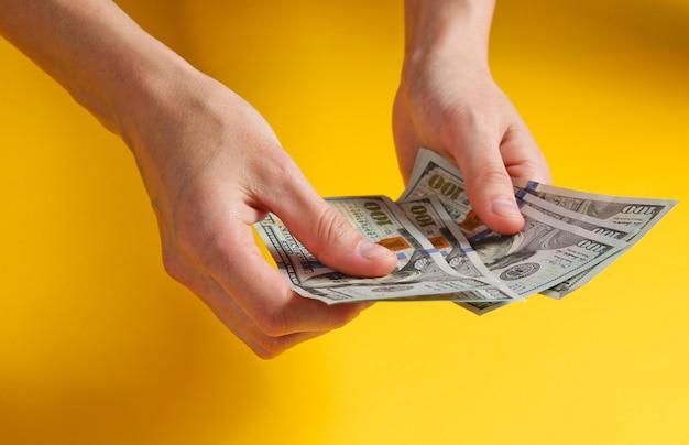 Weibliche hand, die hundert dollarnoten auf gelb zählt.