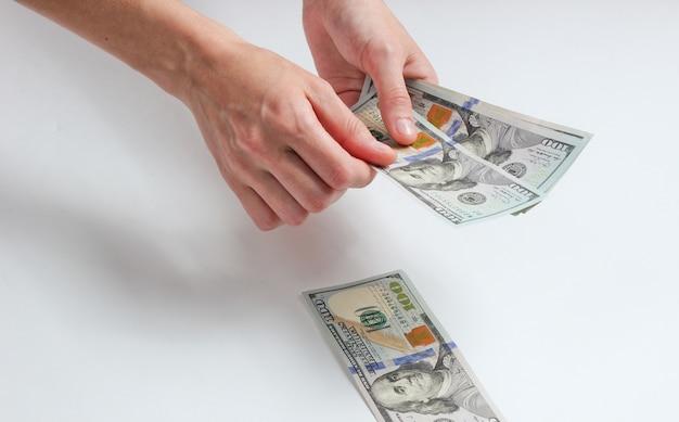Weibliche hand, die hundert dollarnoten auf weiß zählt.