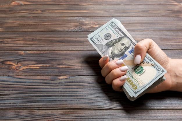 Weibliche hand, die hundert dollarnoten gibt