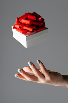 Weibliche hand, die in die luft wirft oder weiße geschenkbox mit roter schleife auf grauem hintergrund fängt. schwebendes geschenk, vertikal