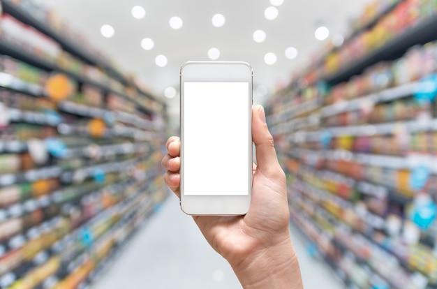 Weibliche hand, die intelligentes mobiltelefon auf supermarktunschärfehintergrund hält