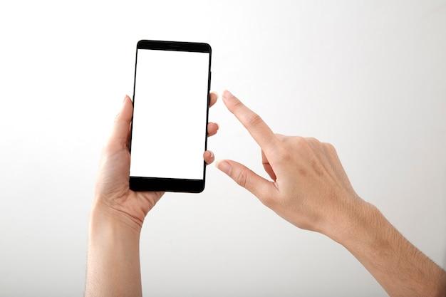 Weibliche hand, die intelligentes telefon des modells hält