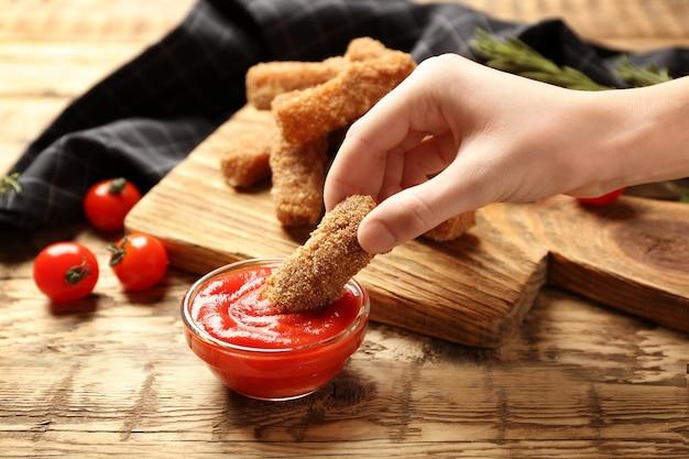 Weibliche hand, die käsestick mit ketchup hält