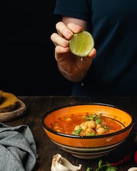Weibliche hand, die kalk in der vegetarischen oder veganen suppe des gemüses, der linsen und der kichererbsen zusammendrückt