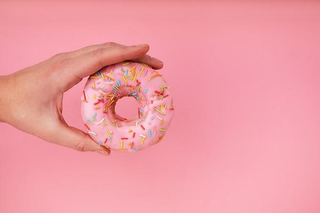 Weibliche hand, die köstlichen donut auf rosa hintergrund hält