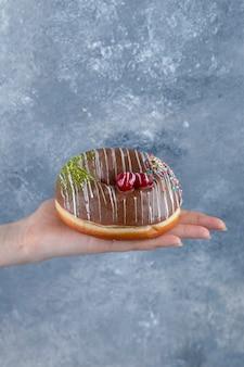 Weibliche hand, die köstlichen schokostreusel donut auf marmoroberfläche hält.