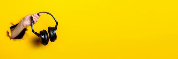 Weibliche hand, die kopfhörer auf einem hellen gelben hintergrund hält