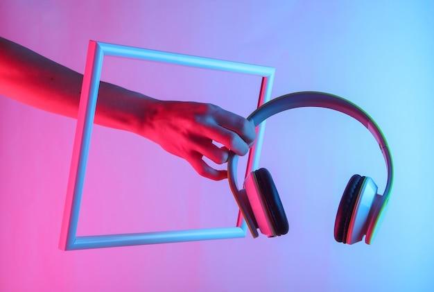 Weibliche hand, die kopfhörer durch einen hochfliegenden rahmen mit holographischem neonlicht hält